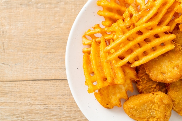 Gebratene chicken nuggets mit bratkartoffeln auf teller