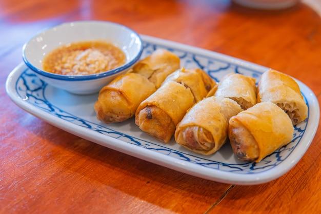 Gebratene chinesische frühlingsrollen mit süßer chilisauce.