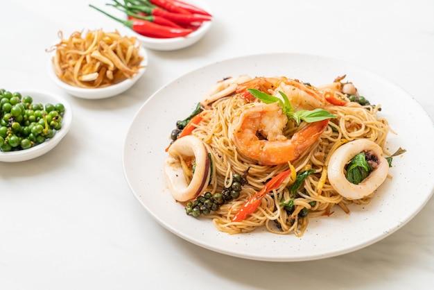 Gebratene chinesische nudeln mit basilikum, chili, garnelen und tintenfisch - asiatische küche