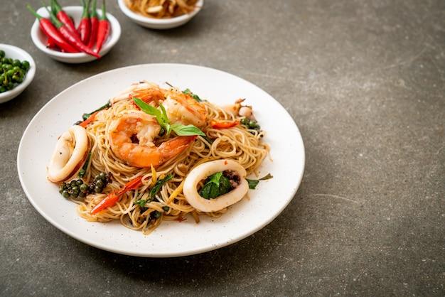Gebratene chinesische nudeln mit basilikum, chili, garnelen und tintenfisch. asiatischer essensstil