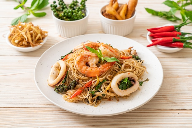 Gebratene chinesische nudeln mit basilikum, chili, garnelen und tintenfisch