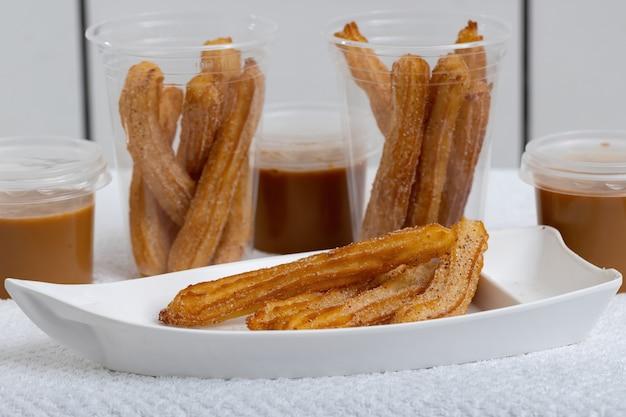 Gebratene churros-süßigkeiten mit zucker auf weiß