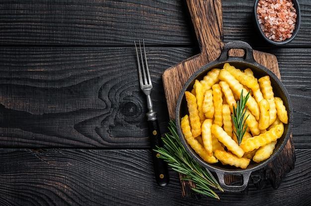 Gebratene crinkle-pommes-frites-kartoffeln in einer pfanne
