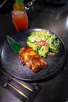 Gebratene ente mit salat auf einem schwarzen teller