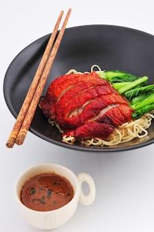 Gebratene entennudeln mit sauce chinesischer küche auf weißem hintergrund