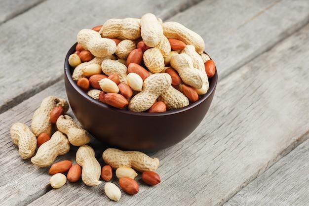 Gebratene erdnüsse im oberteil und in einer schale, gegen einen grauen holztisch abgezogen
