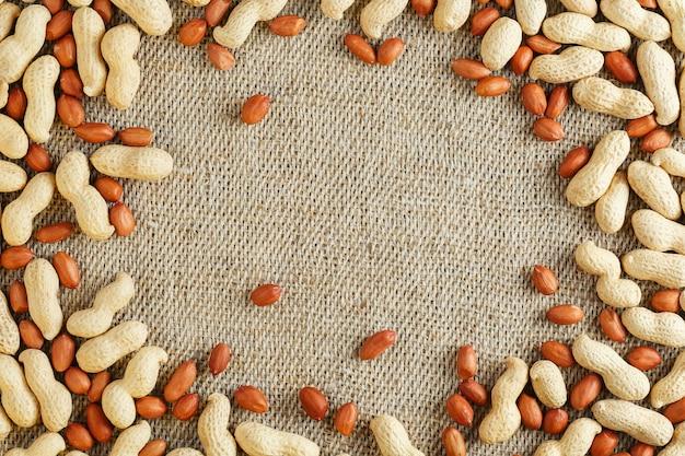 Gebratene erdnüsse in einer schale und geschält auf einem braunen stoff.