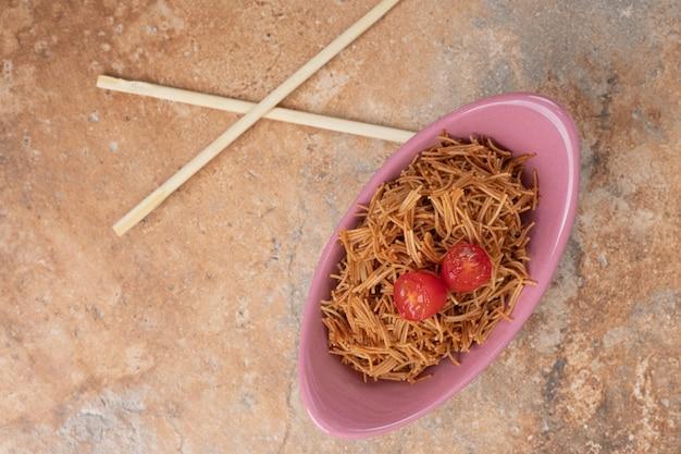 Gebratene fadennudeln mit tomate in rosa schüssel mit stäbchen. hochwertiges foto