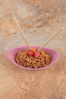Gebratene fadennudeln mit tomate in rosa schüssel mit stäbchen