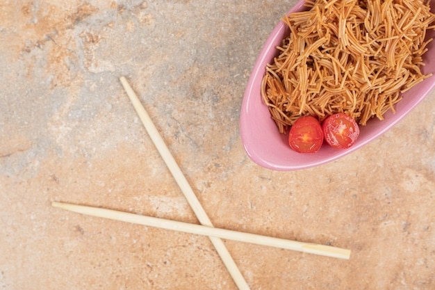 Gebratene fadennudeln mit tomaten in rosa schüssel mit stäbchen.