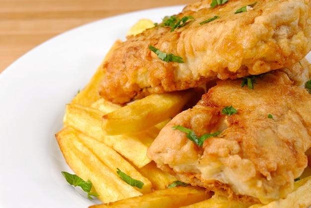 Gebratene fish and chips auf weißem teller