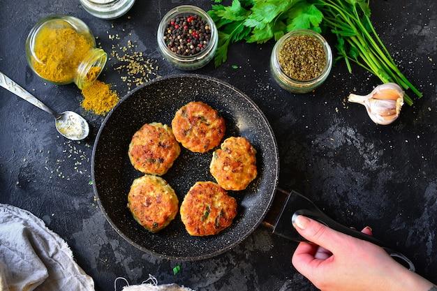 Gebratene fleischbällchen in einer pfanne. hühnerschnitzel in einer pfanne auf einem dunklen betontisch. draufsicht. zutaten und gekochte fleischbällchen. gewürze, petersilie, fleischgericht. eine frau hält eine pfanne mit essen.