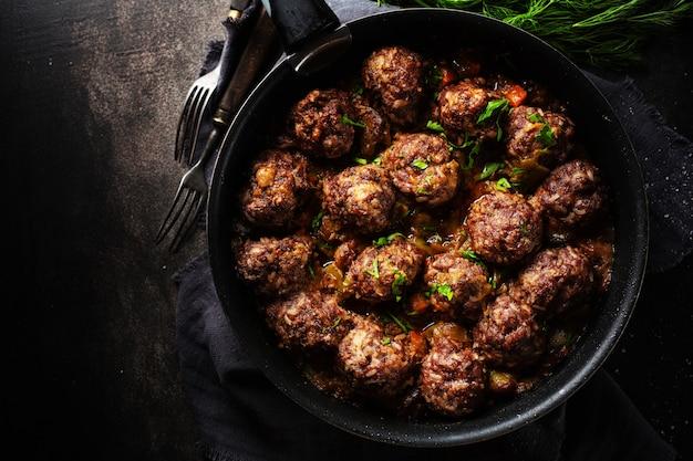 Gebratene fleischbällchen mit sauce auf der pfanne