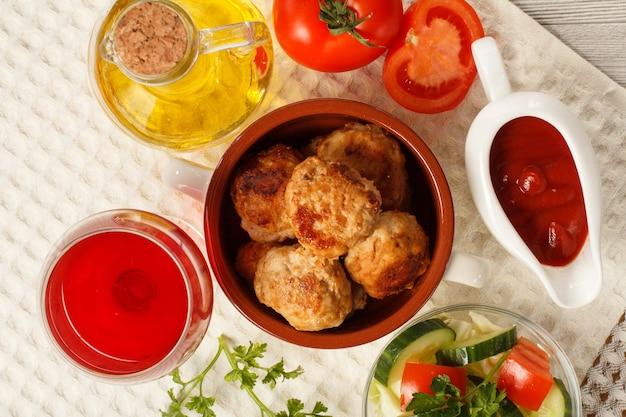 Gebratene fleischkoteletts in keramikschüssel, keramiksaucenboot mit tomatensauce, salat aus frischen gurken und tomaten, glas rotwein, glasflasche mit sonnenblumenöl auf weißem küchentuch. ansicht von oben
