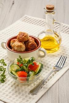 Gebratene fleischkoteletts in keramischer suppenschüssel, flasche mit sonnenblumenöl und salat aus frischen gurken und tomaten in glasschüssel, dekoriert mit frischer petersilie und gabel auf weißem küchentuch