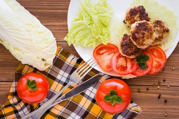 Gebratene fleischpastetchen, tomaten und peking-kohl auf einem holztisch, draufsicht
