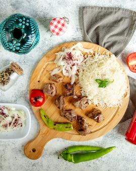 Gebratene fleischstücke mit geschnittener zwiebel und reis