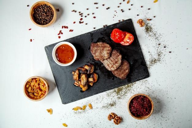 Gebratene fleischstücke und gebratene pilze