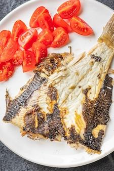 Gebratene flunder gegrillter gebackener fisch meeresfrüchte tomatengemüse zweiten gang