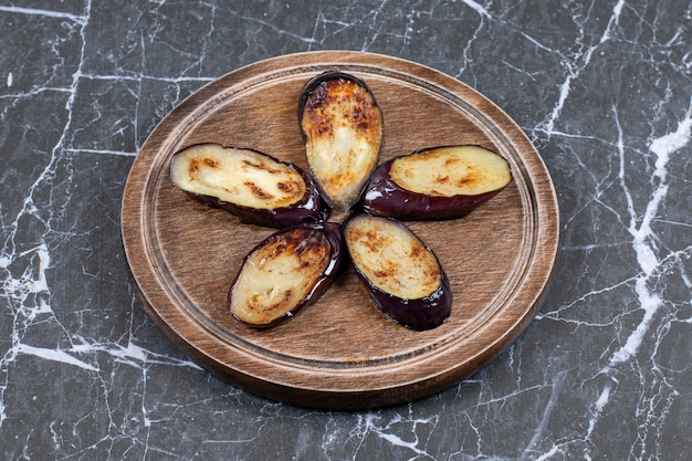 Gebratene frische auberginenscheiben auf holzbrett.