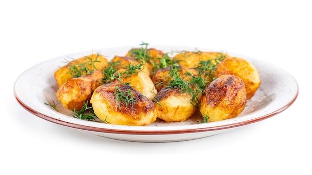Gebratene frische kartoffeln und dill auf einem teller isoliert. hausmannskost