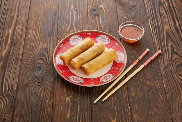 Gebratene frühlingsrollen mit saucen aus rotem pfeffer, serviert in einem traditionellen porzellanteller mit holzstäbchen über einem holztisch. draufsicht flache lage, kopieren raum asiatisches nahrungsmittelkonzept