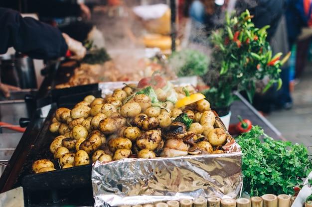 Gebratene ganze kartoffeln mit gemüse auf einem lebensmittelmarkt