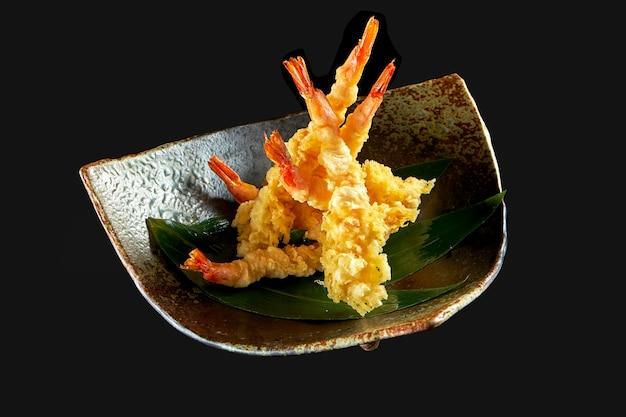 Gebratene garnelen-garnelen-pommes in tempura, serviert in einer schwarzen schüssel nach japanischer art