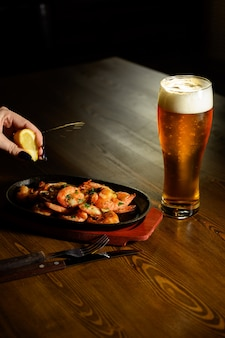 Gebratene garnelen mit frischem rosmarin und zitronensaft und einem glas bier