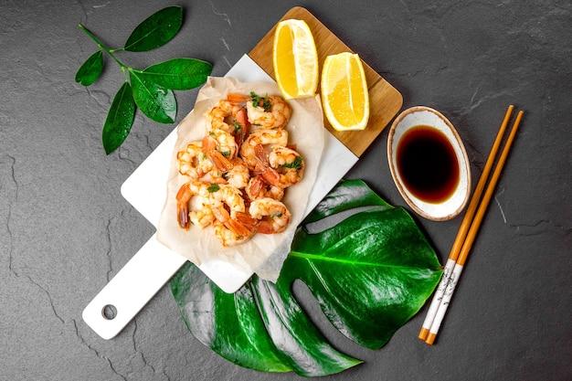 Gebratene garnelen mit zitronen-soja-sauce auf einem schneidebrett und grünem monstera-blatt, draufsicht