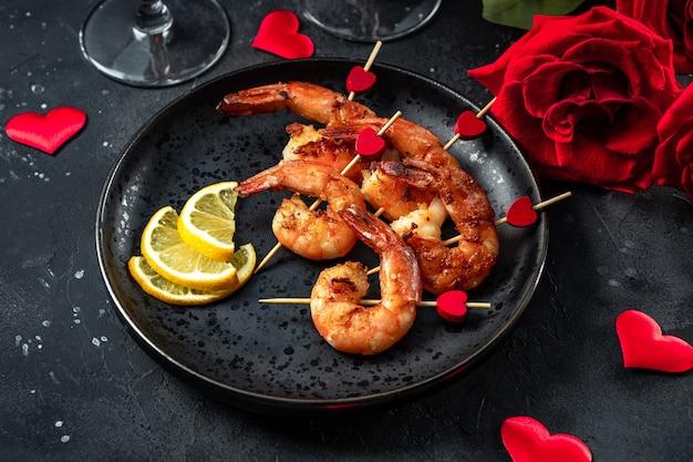 Gebratene garnelen, rosen und champagner auf dem schwarzen hintergrund. ursprüngliche vorspeise für valentinstag, romantisches abendessen. hochwertiges foto