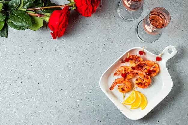 Gebratene garnelen, rosen und champagner. original essen zum valentinstag, romantisches abendessen. draufsicht, freier platz für text. hochwertiges foto