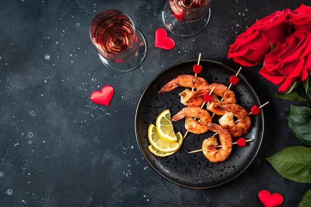 Gebratene garnelen, rosen und champagner. ursprüngliche vorspeise für valentinstag, romantisches abendessen. draufsicht, freier platz für text. hochwertiges foto