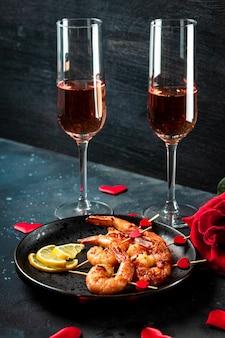 Gebratene garnelen, rosen und champagner. ursprüngliche vorspeise für valentinstag, romantisches abendessen, vertikales foto. hochwertiges foto