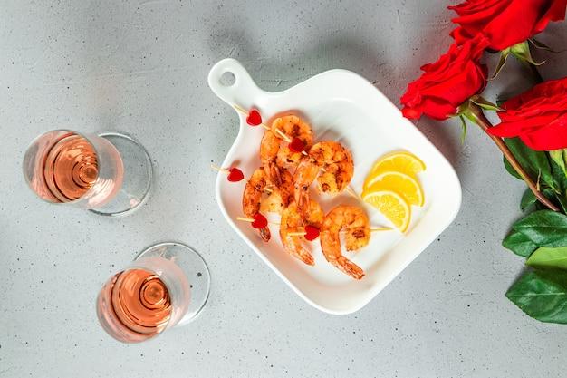 Gebratene garnelen, rosen und champagner. ursprüngliche vorspeise für valentinstag, romantisches abendessen