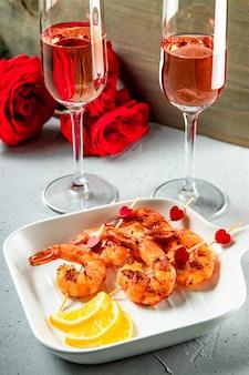 Gebratene garnelen, rosen und zwei gläser champagner. ursprüngliche vorspeise für valentinstag, romantisches abendessen. hochwertiges foto