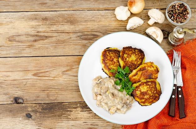 Gebratene geriebene kartoffelpuffer mit pilzsauce. studiofoto.