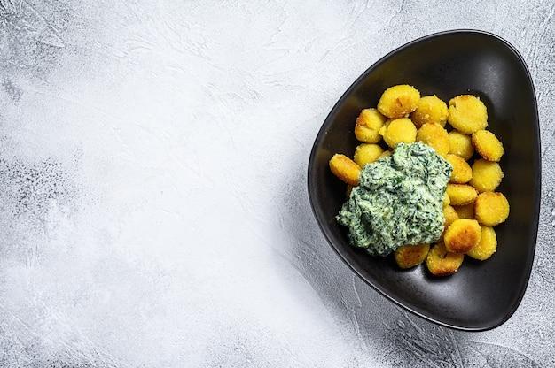 Gebratene gnocchi-kartoffelnudeln mit spinat