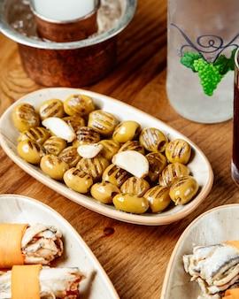 Gebratene grüne oliven mit knoblauch