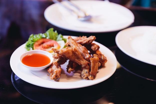 Gebratene hähnchenflügel mit salz serviert mit chilisauce.