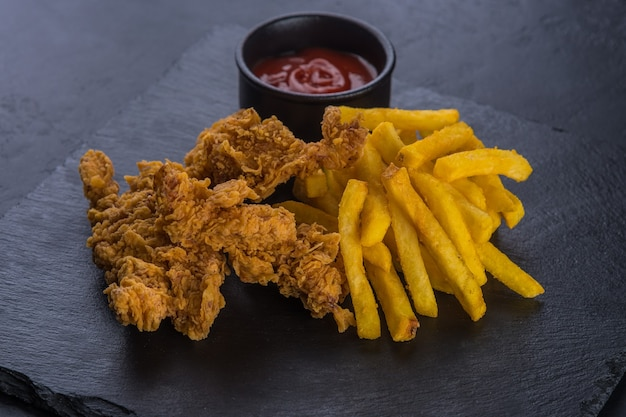 Gebratene hähnchenflügel, paniert mit pommes frites und ketchup