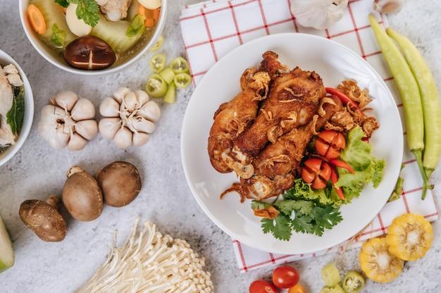 Gebratene hähnchenkeule mit tomate, chili, gebratenen zwiebeln, salat, mais und nadelpilz.