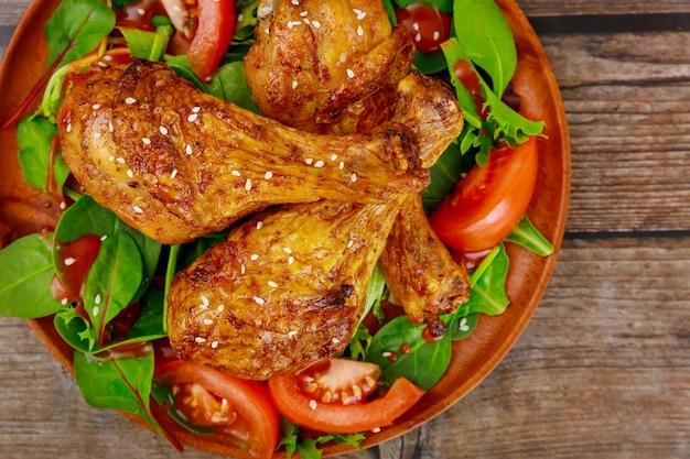 Gebratene hähnchenkeulen mit salat auf rustikalem holztisch. draufsicht.
