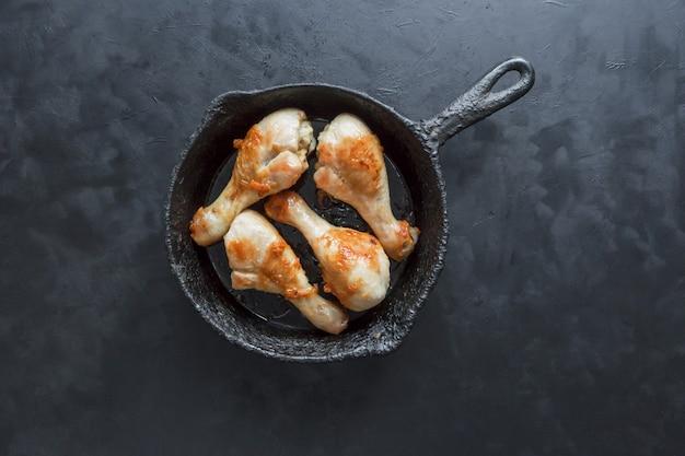 Gebratene hähnchenschenkel auf einem schwarzen tisch in einer alten pfanne.