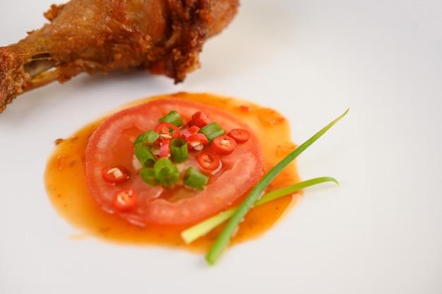 Gebratene hähnchenschenkel auf einem weißen teller mit sauce.