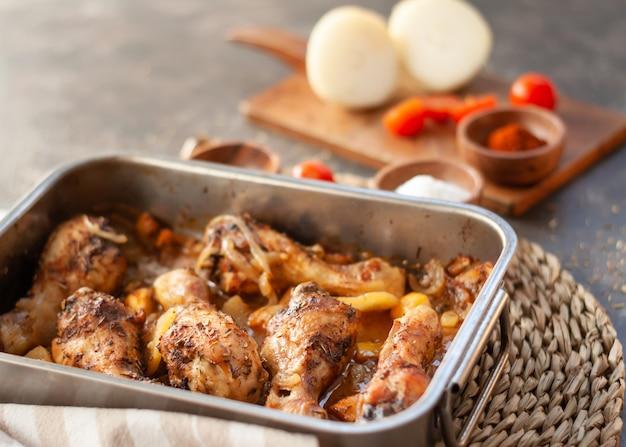 Gebratene hähnchenschenkel auf metallbackblech mit kartoffeln, zwiebeln. tomaten mit gewürzen. nahaufnahme mit kopierraum.