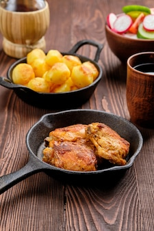 Gebratene hähnchenschenkel, bratkartoffeln und salat - rustikales abendessen