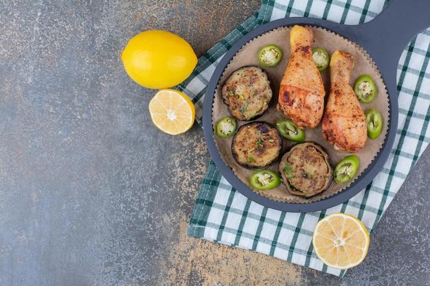 Gebratene hähnchenschenkel mit gebratenem gemüse und zitrone auf dunklem brett. foto in hoher qualität