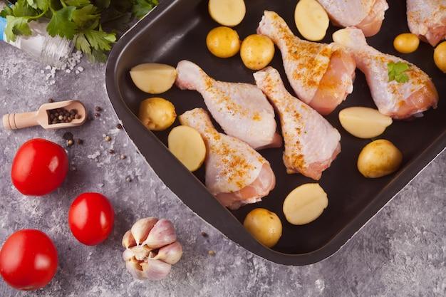 Gebratene hähnchenschenkel mit kartoffeln, gewürzen und kräutern auf der schwarzen pfanne.