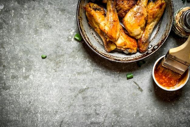 Gebratene hähnchenschenkel mit tomatensauce auf dem steintisch